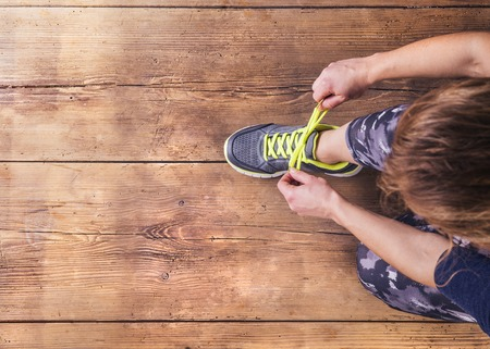 Photo for Unrecognizable young runner tying her shoelaces. Studio shot on wooden floor background. - Royalty Free Image
