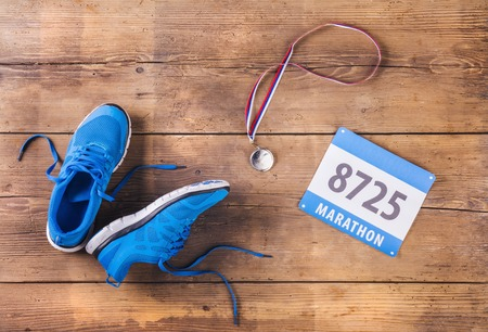 Photo pour Pair of running shoes, medal and race number on a wooden floor background - image libre de droit