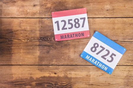 Photo pour Two marathon race number laid on a wooden floor background - image libre de droit