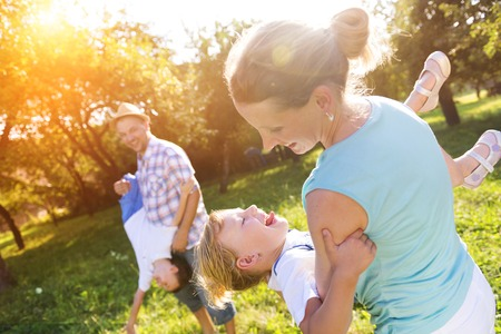 Photo for Happy young family spending time together outside in green nature. - Royalty Free Image