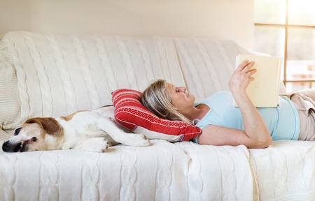 Photo pour Senior woman with her dog on a couch inside of her house. - image libre de droit