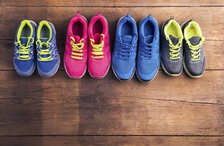 Photo pour Four pairs of various running shoes laid on a wooden floor background - image libre de droit