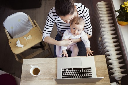 Photo for Young mother in home office with computer and her daugher - Royalty Free Image