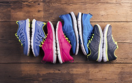 Photo pour Four pairs of various running shoes laid on a wooden floor background - image libre de droit