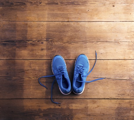 Photo pour Pair of blue running shoes laid on a wooden floor background - image libre de droit