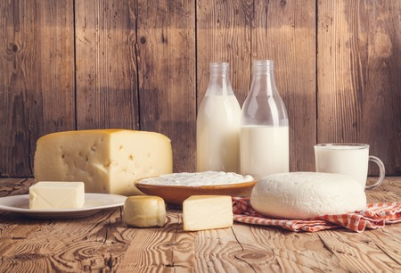 Photo for Variety of dairy products laid on a wooden table background - Royalty Free Image