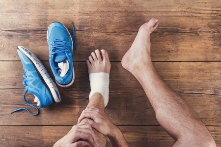 Photo pour Unrecognizable injured runner sitting on a wooden floor background - image libre de droit