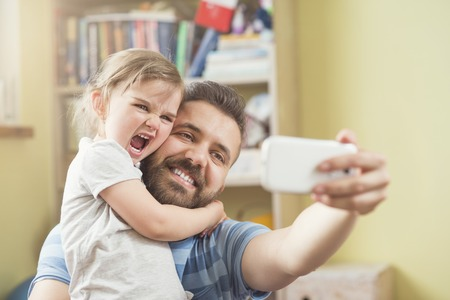 Foto de Young father with his cute little daughter taking selfie - Imagen libre de derechos