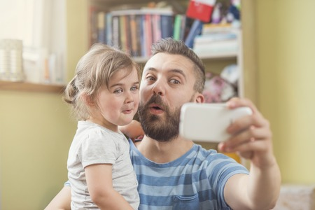 Photo pour Young father with his cute little daughter taking selfie - image libre de droit