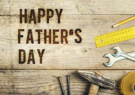 Foto de Desk of a carpenter with Happy fathers day sign. Studio shot on a wooden background. - Imagen libre de derechos