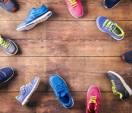 Photo pour Various running shoes laid on a wooden floor background - image libre de droit