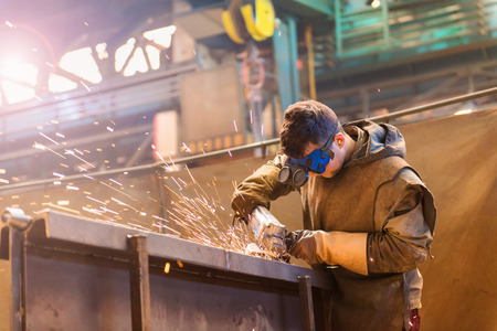 Photo pour Young man with protective goggles welding in a factory - image libre de droit