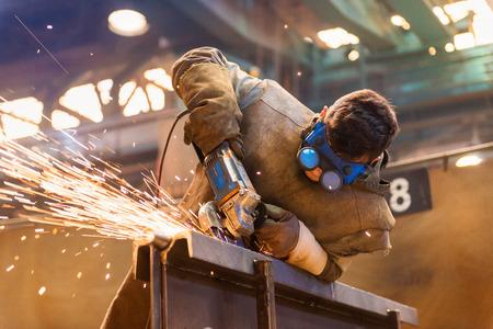 Foto de Young man with protective goggles welding in a factory - Imagen libre de derechos