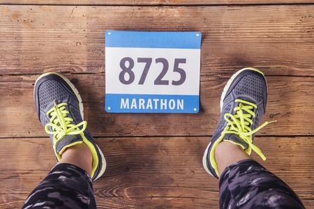 Photo pour Unrecognizable young runner. Studio shot on wooden background. - image libre de droit
