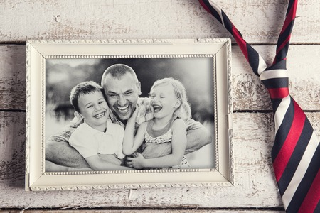 Photo for Picture frame with family photo and colorful tie laid on wooden background. - Royalty Free Image