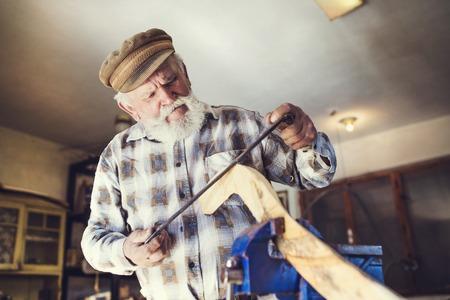 Photo pour Senior craftsman working with planer on wooden pole in his workshop - image libre de droit