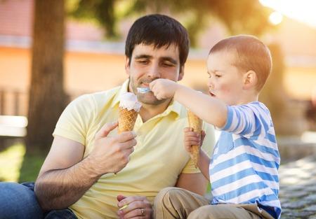 Foto de Father and son enjoying ice cream outside in a park - Imagen libre de derechos
