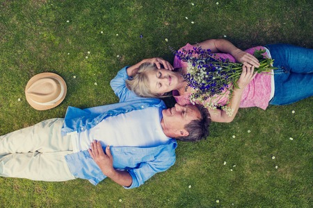 Foto de Beautiful seniors lying on a grass in a park hugging - Imagen libre de derechos