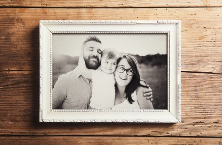 Photo for Fathers day composition - picture frame with a black and white photo. Studio shot on wooden background. - Royalty Free Image