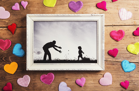 Photo pour Fathers day composition - picture frame and colorful hearts on the floor. Studio shot on wooden background. - image libre de droit