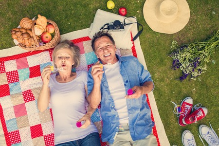Photo pour Beautiful seniors having a picnic in nature and blowing bubbles - image libre de droit