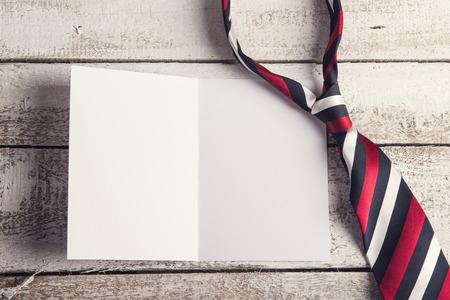 Foto de Fathers day composition - tie and empty sheet of paper. Studio shot on wooden background. - Imagen libre de derechos