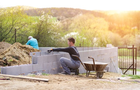 Photo pour Bricklayer putting down another row of bricks in site - image libre de droit