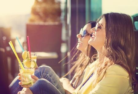 Photo pour Two beautiful women having fun in a bar - image libre de droit