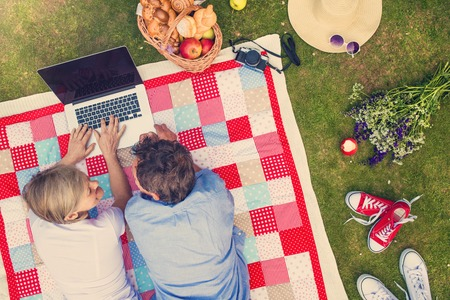 Photo pour Beautiful seniors with notebook having a picnic in nature - image libre de droit