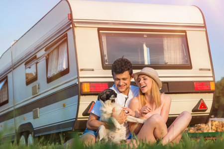 Photo for Beautiful young couple in front of a camper van on a summer day - Royalty Free Image