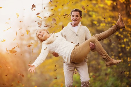 Photo pour Active seniors having fun and playing with the leaves in autumn forest - image libre de droit