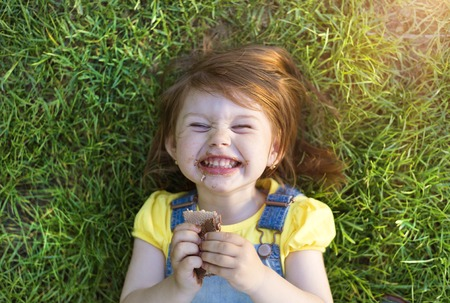 Photo pour Cute little girl with chocolate face lying on a grass - image libre de droit