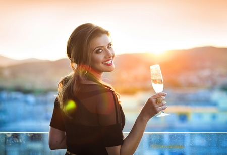 Photo pour Attractive young woman with a drink on a terrace of a bar - image libre de droit
