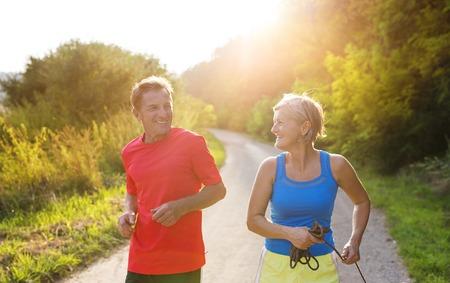 Photo pour Active seniors running outside in green nature - image libre de droit