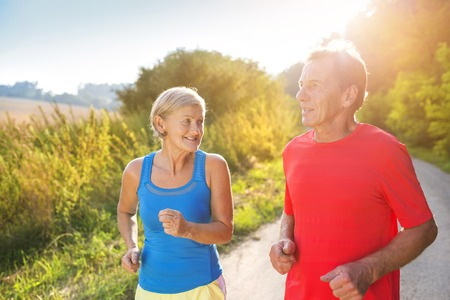 Photo pour Active seniors running outside in green nature - image libre de droit