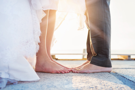 Photo pour Feet of a bride and groom standing on the pier - image libre de droit