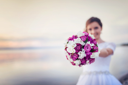 Foto de Beautiful bride with bouquet standing on the beach - Imagen libre de derechos