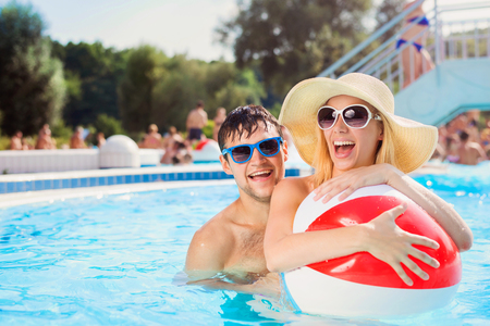 Photo for Beautiful young couple having fun outside in the swimming pool - Royalty Free Image