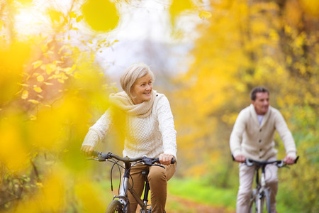 Photo pour Active seniors riding bikes in autumn nature. They having romantic time outdoor. - image libre de droit