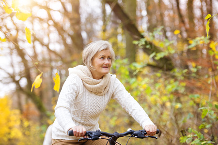 Photo for Active senior woman riding bike in autumn nature. They having romantic time outdoor. - Royalty Free Image