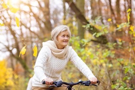 Foto für Active senior woman riding bike in autumn nature. They having romantic time outdoor. - Lizenzfreies Bild