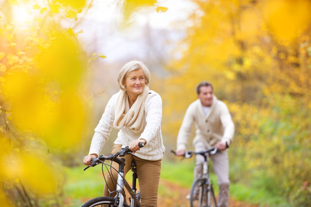 Foto de Active seniors riding bikes in autumn nature. They having romantic time outdoor. - Imagen libre de derechos