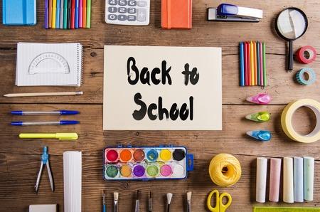 Foto de Desk with stationary and with Back to school sign. Studio shot on wooden background. - Imagen libre de derechos
