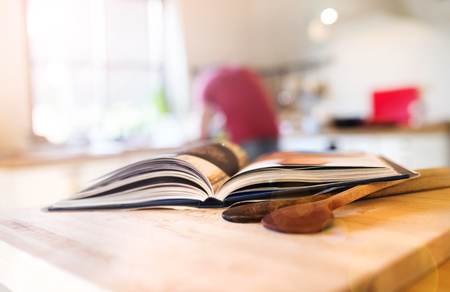 Photo pour Cook book laid on a kitchen table with two wooden spoons - image libre de droit