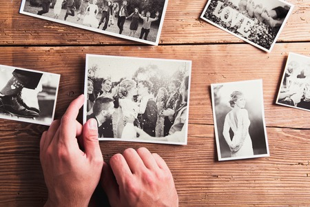 Photo pour Wedding photos laid on a table. Studio shot on wooden background. - image libre de droit
