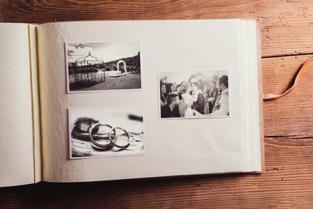 Foto de Wedding photos in album. Studio shot on wooden background. - Imagen libre de derechos