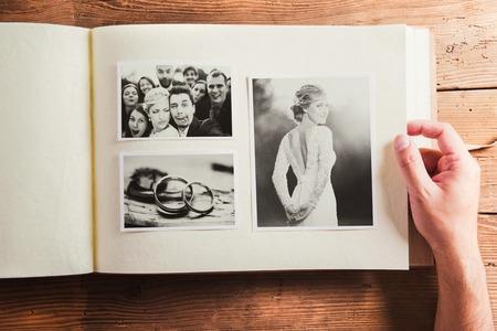 Photo pour Wedding photos in album. Studio shot on wooden background. - image libre de droit