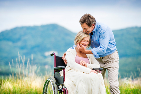 Photo pour Senior man with woman in wheelchair outside in nature - image libre de droit