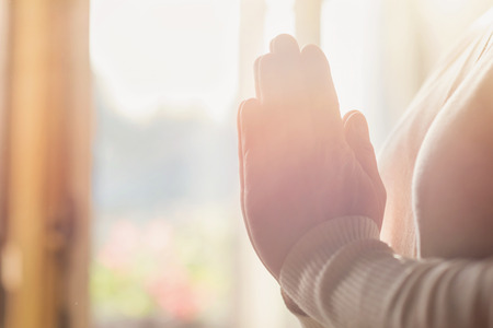 Photo pour Hands of an unrecognizable woman standing by the window and praying - image libre de droit