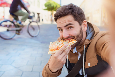 Foto per Handsome young man eating a slice of pizza outside on the street - Immagine Royalty Free